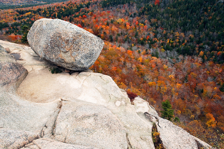 A boulder known as Bubble Rock rests on one of The Bubbles with fall colored forest below, Mount Desert Island, Acadia National Park, near Bar Harbor, Maine, USA