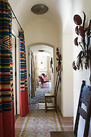 In the corridor leading to the bedrooms the curtains are made from Mexican serape blankets stitched to a Kathryn Ireland red ribbed fabric