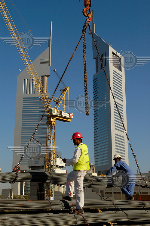 Construction labourers work infront of the Emirates Towers beside the Sheikh Zayed Road.