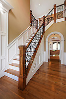 Traditional two story entry foyer with staircase and custom oak and wrought iron railing.