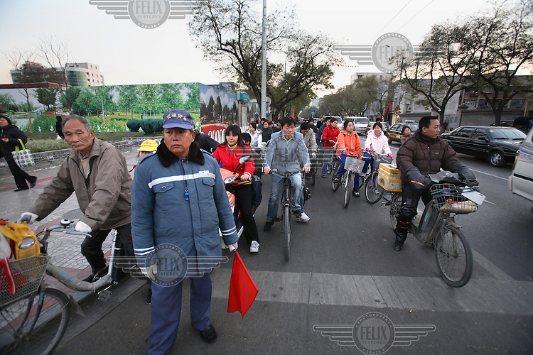 A traffic guard stands amongst cyclists in a busy Beijing street...