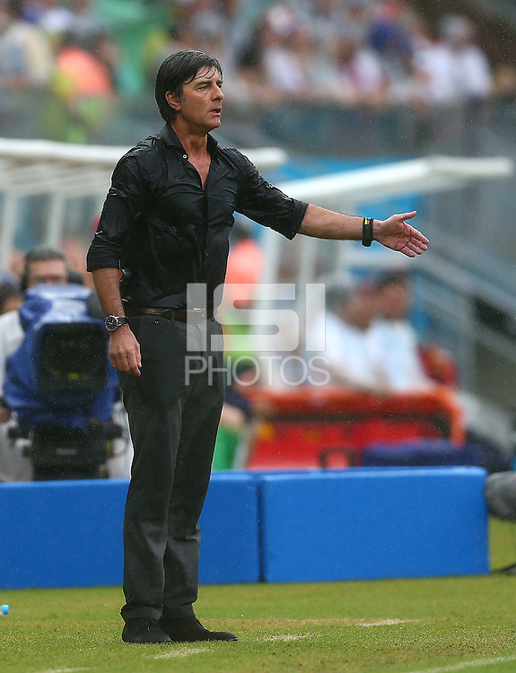 A soaking wet Germany coach Joachim Loew gestures on the touchline