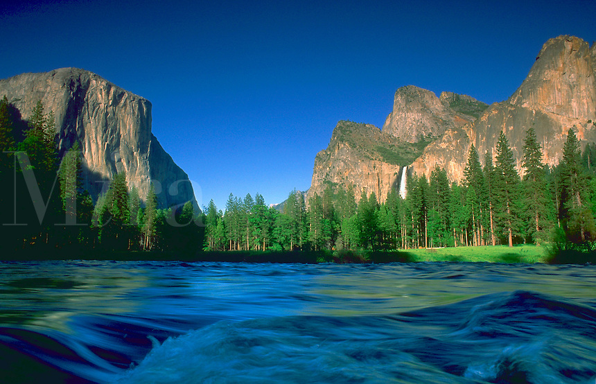 A river running through Yosemite Valley in Yosemite National Park, California. The river run past rocky peaks, forest and a waterfall beneath a blue sky.
