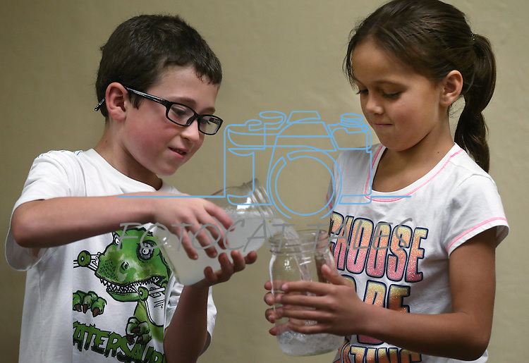 Parker Hale, 6, and Lillian Mendez, 7, help with an experiment during the Mad Science program at the Carson City Library, in Carson City, Nev., on Tuesday, July 15, 2014.<br /> Photo by Cathleen Allison