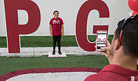 NWA Democrat-Gazette/J.T. WAMPLER James May of Bella Vista takes a photograph of his daughter Kalista May, 10, standing in for the letter i Saturday August 12, 2017 during the RazorbacksÕ annual Fan Day at the University of Arkansas. Football players and coaches were available for autographs with the soccer and volleyball teams.