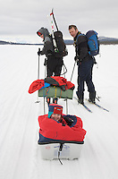 "Sweden, SWE, Kiruna, 2006-Apr-16: Sledging in Lapland: A four years old girl sitting in a ""Pulka"" is being pulled over the frozen Holmajarvi lake by her skiing parents."
