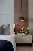 The guest room has a sumptuous feel with neutral furnishing and bedding. A light hangs above the bedside cabinet.