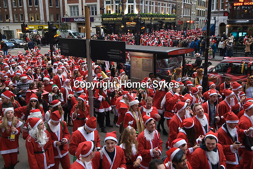 SantaCon meet up outside Liverpool Street Station central city of London UK 2015.