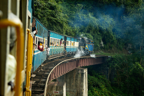 India, Tamil Nadu. The Nilgiri Mountain Railway with its steam locomotive is crossing one of the many bridges between Coonoor and Metapulayam. Part of the journey is managed only by a rack-and-pinion system. --- Info: The Nilgiri Mountain Railway (NMR) is the only rack railway in India and connects the town of Mettupalayam with the hill station of Udagamandalam (Ooty), in the Nilgiri Hills of southern India. The construction of the 46km long meter-gauge singletrack railway in Tamil Nadu State was first proposed in 1854, but due to the difficulty of the mountainous location, the work only started in 1891 and was completed in 1908. This railway, scaling an elevation of 326m to 2,203m and still in use today, represented the latest technology of the time. In July, UNESCO added the NMR as an extension to the World Heritage Site of Darjeeling Himalayan Railway.