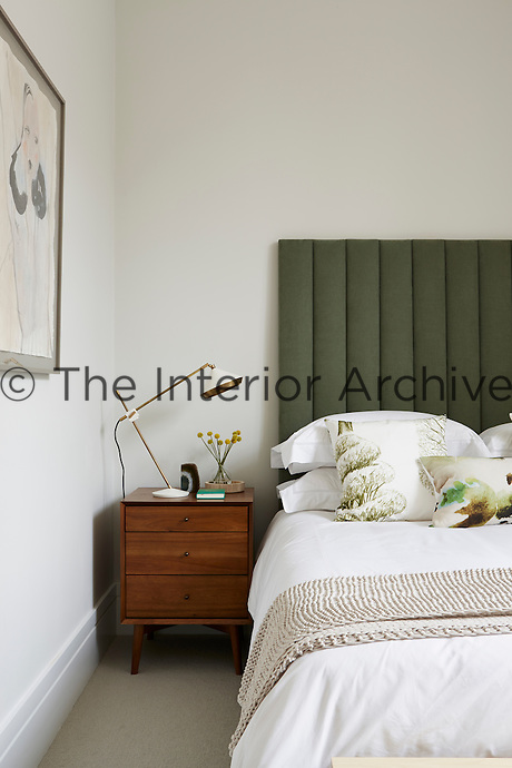 The guest bedroom is decorated in a white and green palette. The double bed has an upholstered headboard and an angle-poise lamp on a wooden bedside chest stands on the side.