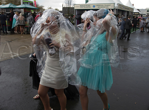 13.04.2012 Aintree, England. The Grand National Festival Ladies Day. Two women racegoers wearing plastic rain covers make their way towards one of the grandstands.