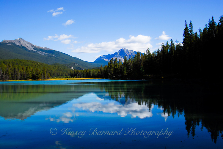 The blue waters of Wabasso lake reflecting clouds, blue skies and the Canadian Rockies