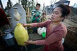 A woman fills a container with water at a community spigot in Makaising, a village in the Gorkha District of Nepal that was hit hard by a devastating 2015 earthquake.