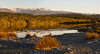 Sunset views of Southern Alps with Aoraki Mount Cook, Mount Tasman and Franz Josef Glacier over coastal lagoon with reflections, Westland Tai Poutini National Park, UNESCO World Heritage Area, West Coast, New Zealand, NZ