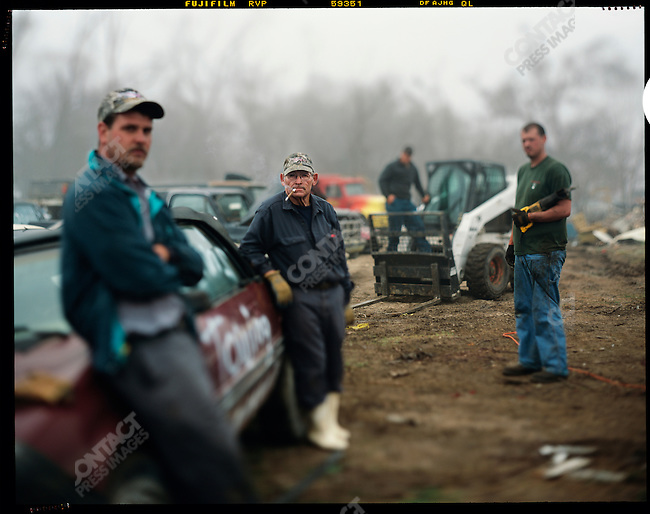 Workers at Johnnies Towing company and the cars they have  towed since the hurricane. Because of the salt water, the cars are virtually useless, save for the Catalytic converters on the bottom, which are salvaged by the workers. Plaquemines Parish, Louisiana, January 2006