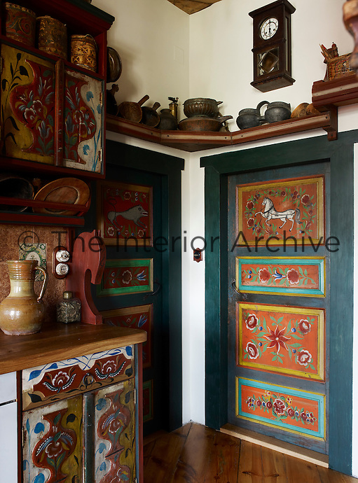 Even the doors in the corner of the kitchen have been decorated with folk-art painted panels to match the kitchen cabinets