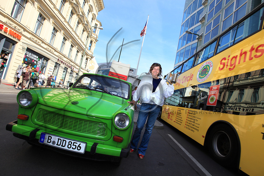 Erica Mayr, jeune femme de 37 ans pose avec une Trabant, une ruche et un enfumoir devant Check point Charlie. Cette jeune femme a fait un buzz médiatique en 2010 quand elle a posé ses premières ruches sur les toits d'un hangar à Berlin. Apicultrice depuis seulement 3 ans, Erica est propriétaire d'un bar branché dans le quartier de Kreuzberg. Aujourd'hui, Erica est heureuse car les abeilles et l'apiculture s'harmonise avec son métier et sa formation universitaire de paysagiste et d'horticulture./// Erica Mayr, 37 years old, posing with a Trabant, a hive and a smoker in front of Checkpoint Charlie. This young woman got the media buzzing when she placed her first hives on the roof of a warehouse in Berlin. Beekeeper since only 3 years ago, Erica is the owner of a trendy bar in the Kreuzberg neighborhood. Today, Erica is happy, because the bees and beekeeping are in line with her profession and university education as a landscaper and horticulturist.