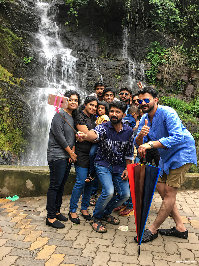 Tourists use a selfie stick to get everyone into the picture while visiting Valanjanganam Falls in Peerumedu, Kerala, India,  June 09, 2017 (Cellphone Photo by Cheryl Senter)