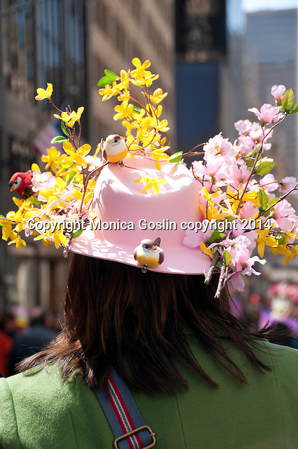 Woman wearing a green coat and a large pink hat decorated with flowers and birds in the Easter Parade on Fifth Avenue in New York City