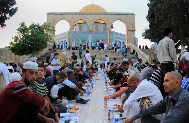 Palestinian muslims prepare to break their fast during the holy fasting month of Ramadan in front of the Dome of the Rock mosque at the al-Aqsa mosque compound, in Jerusalem's old city on June 25, 2016. Ramadan is sacred to Muslims because it is during that month that tradition says the Koran was revealed to the Prophet Mohammed. The fast is one of the five main religious obligations under Islam. More than 1.5 billion Muslims around the world will mark the month, during which believers abstain from eating, drinking, smoking and having sex from dawn until sunset. Photo by Mahfouz Abu Turk