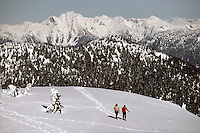 Two Hikers hiking in Snow, Mount Seymour Provincial Park, North Vancouver, BC, British Columbia, Canada - Coast Mountains, Winter / Spring