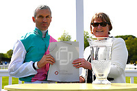 Pat Dobbs, jockey of Sun Maiden, receives his prize from sponsors for winning The Smith & Williamson Fillies' Novice Stakes (Class 5) during Afternoon Racing at Salisbury Racecourse on 17th May 2018