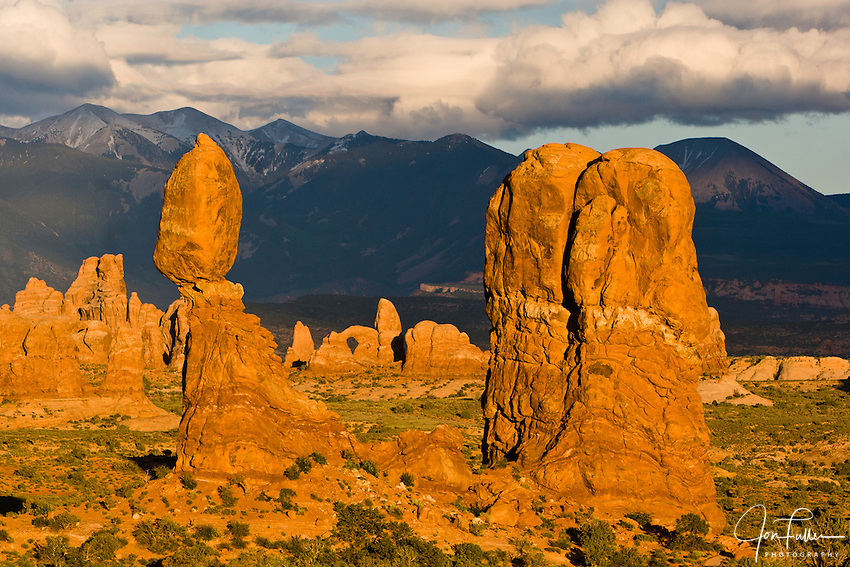 Telephoto view of Balanced Rock, Turret Arch, and the La Sal Mountains, Arches National Park, Moab, Utah, USA with clouds at sunset.