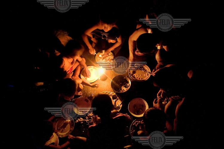 A family eats dinner in a slum area near the 'Smokey Mountain' rubbish dump.