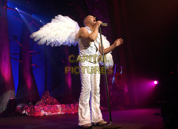 ERASURE -  ANDY BELL .Performing live to a sold out crowd at The Grove of Anaheim in Anaheim, California  .May 18th, 2005.full length stage concert music wings angel costume singing white denim vest trousers.www.capitalpictures.com.sales@capitalpictures.com.Supplied By Capital PIctures