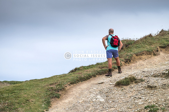 A walker takes a rest and enjoys the view as he walks along the South West Coastal path in Cornwall.
