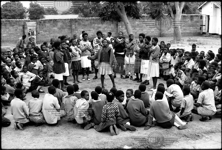 Members of Anti-AIDS club of UNICEF-assisted Hillside Primary School in Lusaka perform for younger pupils in school playground. Members of the club write songs and plays about AIDS prevention.