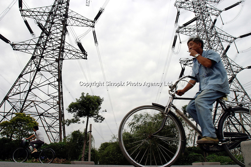 A cyclist pedals past high tension wires near a power plant in Shanghai, China. China needs to invest 100 billion euros in the next five years to generate enough electricity to meet its huge demand for power and reduce crippling power shortages, state media said. Further investments would be needed, including 75 billion euros to improve power grids..