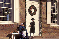 Colonial Williamsburg, Virginia, VA, Williamsburg, Interpreters dressed in colonial costumes talk outside the Courthouse which is decorated with a Christmas wreath in Colonial Williamsburg.