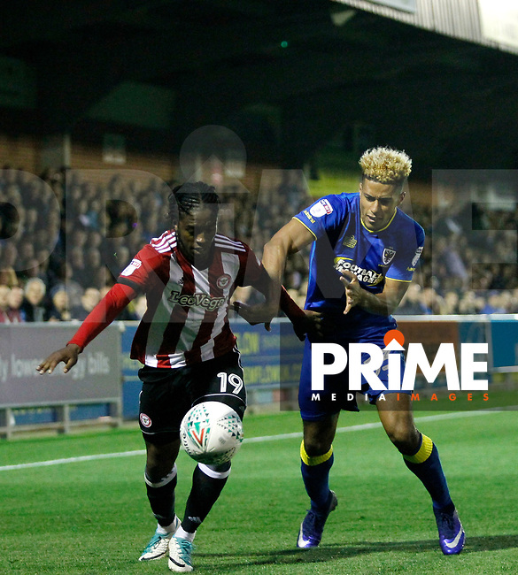 Brentford's Romaine Sawyers holds off AFC Wimbledon's Lyle Taylor during the Carabao Cup match between AFC Wimbledon and Brentford at the Cherry Red Records Stadium, Kingston, England on 8 August 2017. Photo by Carlton Myrie.