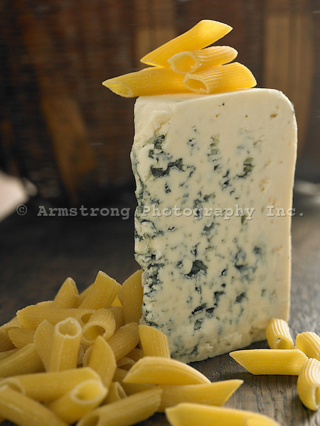 A wedge of blue cheese with uncooked penne pasta.
