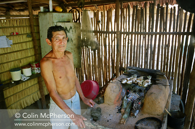 A villager grilling fish in the kitchen of his traditional reed hut in the village of Jaguarari. The Floresta Nacional do Tapajos (FLONA), a 6500 km2 protected reserve, was home to several small communities which lived on the banks of the Rio Tapajos river. The communities did not have electricity or running water and access to the villages was by unpaved dirt roads from Santarem and Highway BR163.