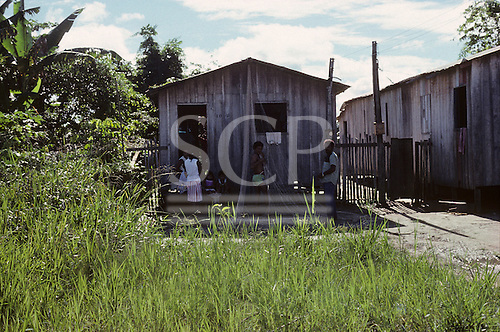 Rio Guama, Amazon, Brazil. Caboclo family outside their wooden shack hut. Para State.