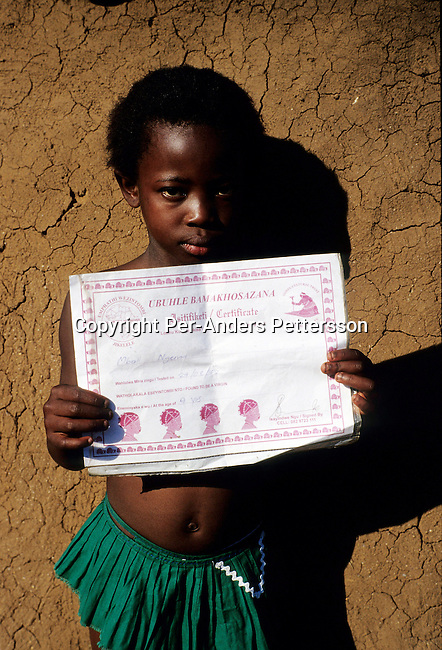 NGUDWINI, SOUTH AFRICA - SEPTEMBER 12: Mbali Ngema, age 9, shows her certificate that say's that she's been tested as a virgin on September 10, 2004 in Ngudwini village in rural Natal, South Africa. Her older sister Nubohle has traveled to the annual Reed Dance where about 20.000 maidens from all over South Africa gathers to dance for the Zulu King. Nbali wants desperately to go to the annual event but she's far to young and has to wait for 3-4 years. The girls come to the kingdom to declare their virginity and the ceremony encourages girls and young women to abstain from sexual activity to curb the spread of HIV-Aids. .(Photo: Per-Anders Pettersson).....