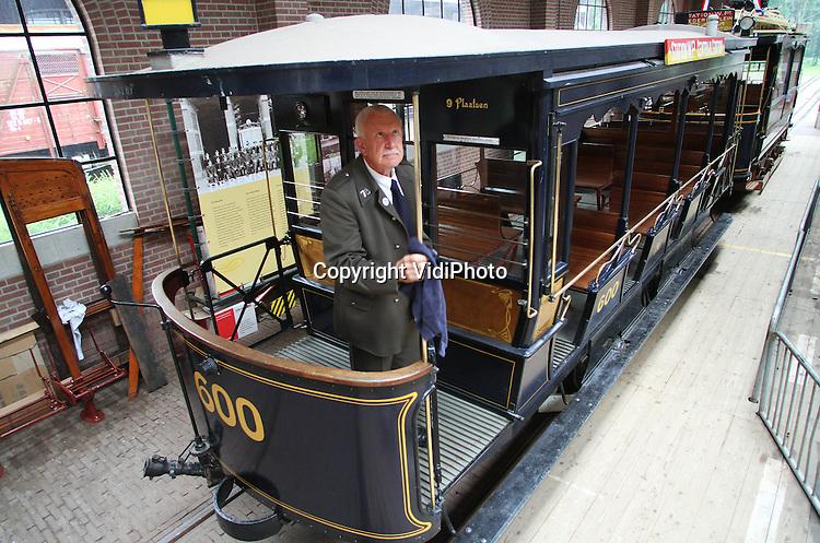 """Foto: VidiPhoto..ARNHEM - Vrijwilliger Ton Kruitbosch van het Nederlands Openluchtmuseum in Arnhem poetst  vrijdagmiddag het koper van de open zomerwagon van de GTr 72, een eeuwenoude Amsterdamse tram. Van de oorspronkelijk 215 trams, die tussen 1902 en 1905 zijn gebouwd, zijn er nog maar drie over. Omdat het Openluchtmuseum dit jaar een eeuw oud is en onlangs daar de """"Amsterdamse Westerstraat"""" is geopend, gaat het kostbare rijtuig vanaf zaterdag tot 12 augustus ieder weekend rijden in het Arnhemse museum. Omdat de GTr 72 een kwetsbaar stuk cultuur erfgoed is, wordt er alleen mee gereden als het droog weer is. Wagon en tram zijn in bruikleen van de Elektrische Museumtramlijn Amsterdam. ."""