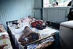 """Lisa regarde par la fenêtre un jeune migrant qui viens d'arriver à Mayotte. Il vit dans un """"banga"""", une petite case de tôle qu'il partage avec 4 personnes, Labattoir, Mayotte, août 2016."""