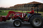 Ford Waterstrat takes his son Finley, 2, for a ride on the tractor as he parks it near the barn for the night. Waterstrat and his wife Amanda said they want to teach Finley as much as they can about the labor and values of farm life.