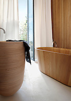 On a tinted concrete floor by Marius Aurenti is a prototype wash basin designed by François Champsaur and a birchwood bath tub by Matteo Thun and Antonio Rodriguez, while the wall of this natural bathroom is clad with an exotic wood by Olivier Tourenc