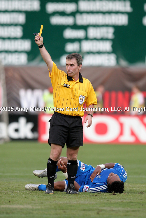 9 July 2005: Referee Michael Kennedy issues a yellow card to Bobby Boswell (not shown) for his foul on Scott Sealy (behind) in the 78th minute. The Kansas City Wizards defeated DC United 1-0 at RFK Stadium in Washington, DC in a regular season Major League Soccer game. . .
