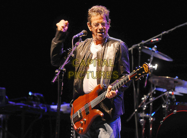 Lou Reed.Performing live at the Hammersmith Apollo, London, England..July 4th, 2011.stage concert live gig performance music half length black leather jacket white top hand arm fist glasses guitar.CAP/BEL.©Tom Belcher/Capital Pictures.
