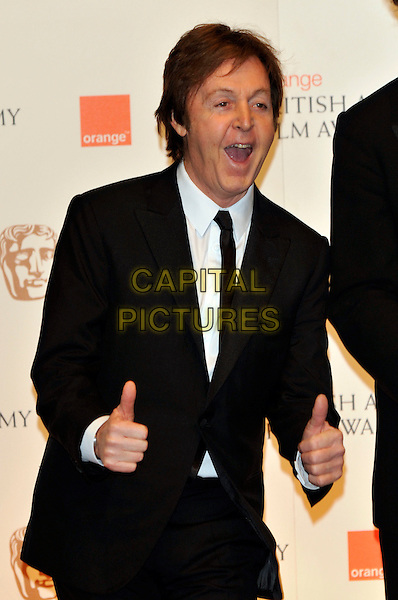 SIR PAUL McCARTNEY.At the 2011 Orange British Academy Film Awards (BAFTAs), Royal Opera House, Covent Garden, London, England, UK, February 13th 2011..press room half length black suit tie hands thumbs up gesture mouth open funny .CAP/PL.©Phil Loftus/Capital Pictures.