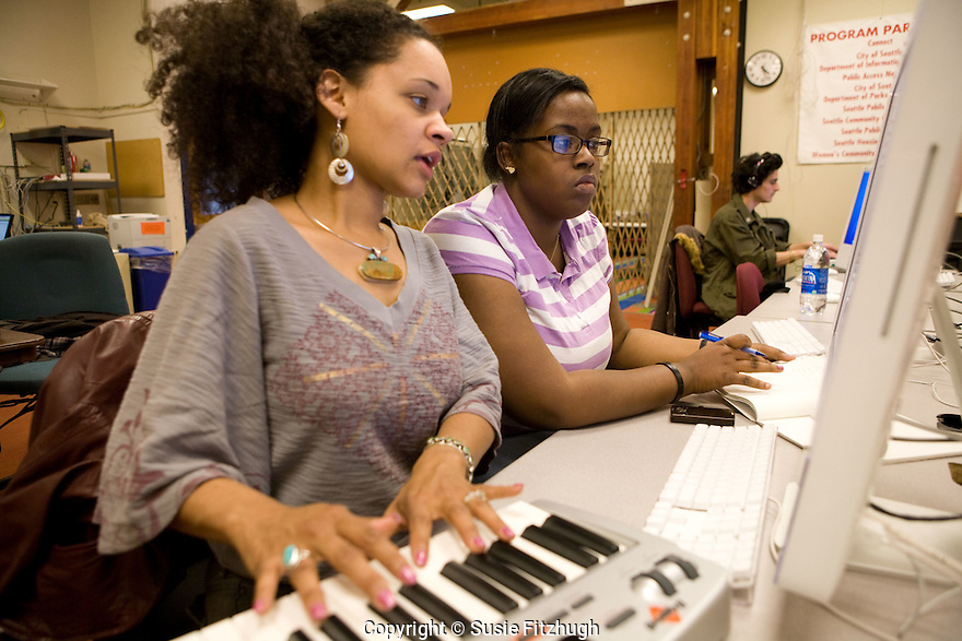Laura 'Piece' Kelly and Lucien Pellegrin work in music production with their Arts /Corps student at Rainier Beach Community Center.