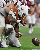 Arkansas Democrat-Gazette/BENJAMIN KRAIN --12/29/14--<br /> Arkansas defender Karl Roesler forces Texas quarterback Tyrone Swoopes to fumbles during the fourth quarter in the Texas Bowl Monday night at NRG Stadium in Houston.