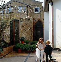 Caroline de Aragues' two children stand in the walled garden with a contemporary water feature behind them
