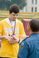 Athlete shaking hands with policeman at award ceremony. Special Olympics U of M Bierman Complex. Minneapolis Minnesota USA