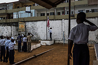 MONROVIA, LIBERIA - FEBRUARY 19: Students salte as they sing the Liberian national anthem during assembly on the fourth day of school, since schools closed due to the Ebola outbreak 6 months ago, at the C.D.B. King Elementary School on February 19, 2015 in Monrovia, Liberia. Though Ebola cases have receded into the single digits in Liberia, lingering fear and a depressed economy have dampened the turnout at schools. Many have yet to reopen, having failed to meet the minimum requirements put in place to prevent the transmission of the virus. Many of those that have reopened – like C.D.B. King, which, though located in the center of the capital, lacks electricity and running water, and has only a few toilet stalls for a student population that numbered 1,000 before Ebola — are struggling.<br /> Daniel Berehulak for The New York Times